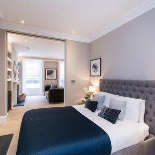 Imagen de dormitorio principal, contemporáneo, pequeño, con paredes grises, suelo de madera clara, estufa de leña, marco de chimenea de piedra y suelo marrón