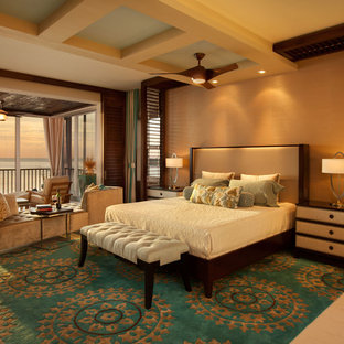 Large contemporary master bedroom in Miami with beige walls and limestone flooring.