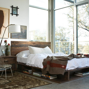Example of an urban concrete floor and gray floor bedroom design in Los Angeles with white walls