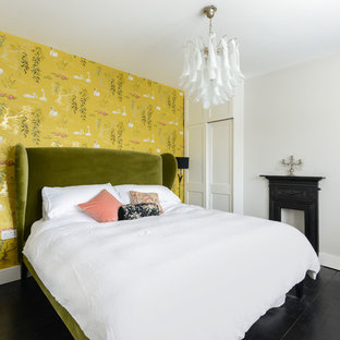 This is an example of a mid-sized transitional bedroom in Kent with multi-coloured walls, black floor and painted wood floors.