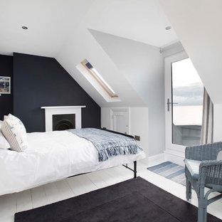 Aménagement d'une grand chambre parentale bord de mer avec un mur blanc, un sol en bois peint, une cheminée standard, un manteau de cheminée en métal et un sol blanc.