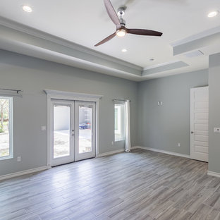 Example of a large beach style master porcelain tile bedroom design in Austin with gray walls and no fireplace