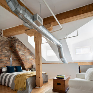Inspiration for a large industrial loft-style light wood floor bedroom remodel in Toronto with white walls