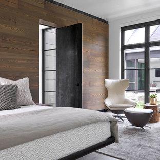 Imagen de dormitorio principal, actual, grande, sin chimenea, con paredes blancas, suelo de cemento y suelo gris