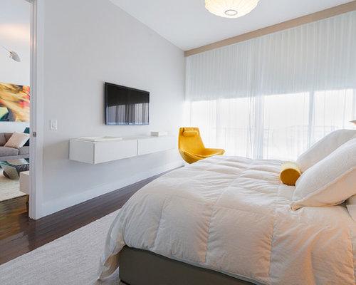 Idée de décoration pour une grande chambre adulte minimaliste avec un mur blanc un sol