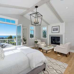 Large coastal master medium tone wood floor and brown floor bedroom photo in Los Angeles with gray walls, a standard fireplace and a tile fireplace