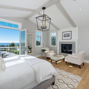 Réalisation d'une grand chambre parentale marine avec un mur gris, un sol en bois brun, une cheminée standard, un sol marron et un manteau de cheminée en carrelage.