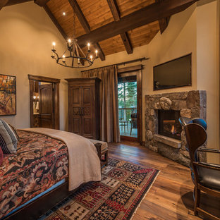 Idee per una grande camera matrimoniale stile americano con pareti beige, parquet scuro, camino classico e cornice del camino in pietra