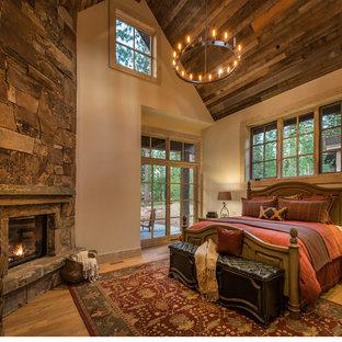 Imagen de dormitorio principal, rural, de tamaño medio, con suelo de madera clara, paredes beige, chimenea tradicional y marco de chimenea de piedra