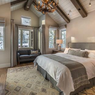 Modelo de dormitorio principal, rural, de tamaño medio, con paredes beige, suelo de madera en tonos medios, chimenea tradicional, marco de chimenea de piedra y suelo marrón