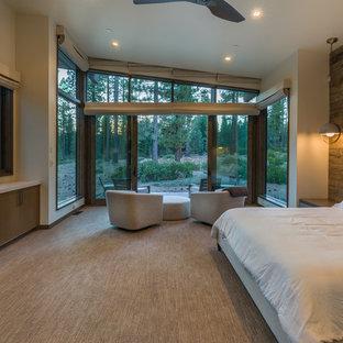 Imagen de dormitorio principal, actual, grande, con moqueta, chimenea tradicional, marco de chimenea de hormigón y suelo beige