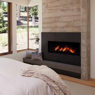 This is an example of a mid-sized contemporary master bedroom in San Francisco with a concrete fireplace surround, a ribbon fireplace, white walls, medium hardwood floors and brown floor.