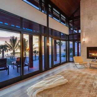 Modelo de dormitorio principal, actual, grande, con paredes beige, suelo de madera en tonos medios, chimenea tradicional y marco de chimenea de baldosas y/o azulejos