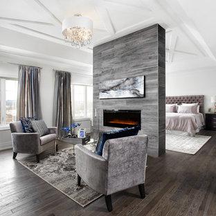 На фото: огромная хозяйская спальня в стиле современная классика с белыми стенами, темным паркетным полом и горизонтальным камином