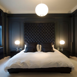 This is an example of a medium sized modern master bedroom in London with black walls, carpet, a corner fireplace and a stone fireplace surround.