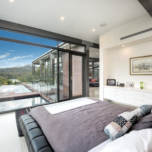 Photo of a contemporary bedroom in Sydney with white walls, concrete floors and grey floor.
