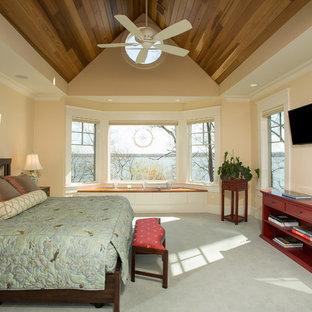 Ejemplo de dormitorio principal, de estilo americano, grande, sin chimenea, con paredes beige, moqueta y suelo verde