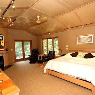 Diseño de dormitorio principal, actual, grande, con chimenea tradicional, marco de chimenea de baldosas y/o azulejos, paredes beige y moqueta