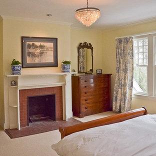 Modelo de dormitorio principal, clásico, grande, con paredes amarillas, moqueta, chimenea tradicional, marco de chimenea de ladrillo y suelo beige