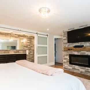 Inspiration pour une grande chambre parentale bohème avec un mur gris, un sol en bois foncé, cheminée suspendue, un manteau de cheminée en carrelage et un sol marron.