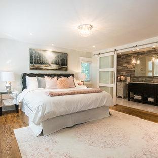 На фото: большая хозяйская спальня в стиле фьюжн с серыми стенами, темным паркетным полом, подвесным камином, фасадом камина из плитки и коричневым полом с