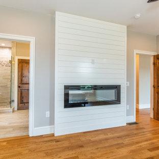 Esempio di una camera matrimoniale costiera di medie dimensioni con pavimento in legno massello medio, camino classico, cornice del camino in perlinato e pavimento marrone