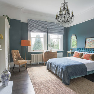 This is an example of a classic master bedroom in Kent with blue walls, dark hardwood flooring and a standard fireplace.