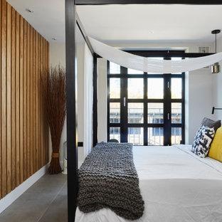 Imagen de dormitorio principal, industrial, de tamaño medio, sin chimenea, con paredes blancas, suelo de baldosas de porcelana y suelo gris