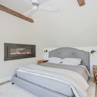 This is an example of a country loft-style bedroom in Other with beige walls, ceramic floors, a ribbon fireplace and grey floor.