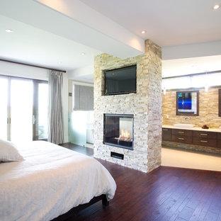 Imagen de dormitorio principal, minimalista, de tamaño medio, con chimenea de doble cara y marco de chimenea de piedra