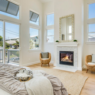Design ideas for a mid-sized beach style master bedroom in Los Angeles with white walls, light hardwood floors, a standard fireplace, a stone fireplace surround and beige floor.
