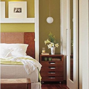 Modelo de dormitorio principal, contemporáneo, de tamaño medio, con paredes verdes y suelo de madera en tonos medios