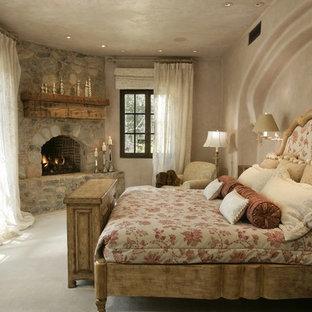 Bild på ett rustikt sovrum, med en öppen hörnspis och en spiselkrans i sten