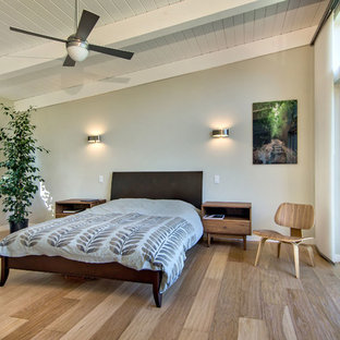 This is an example of a mid-sized midcentury master bedroom in San Francisco with grey walls, light hardwood floors and brown floor.