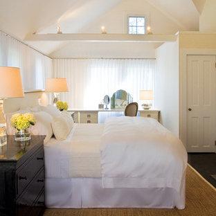 Imagen de dormitorio principal, costero, grande, con paredes blancas, suelo de madera oscura, chimenea tradicional y marco de chimenea de ladrillo