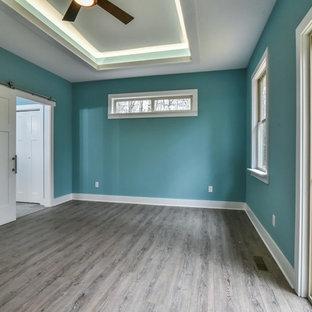 Modelo de dormitorio principal, de estilo americano, de tamaño medio, sin chimenea, con paredes azules, suelo vinílico y suelo marrón