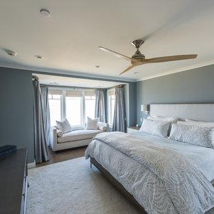Imagen de dormitorio principal, marinero, grande, sin chimenea, con paredes azules, suelo de madera en tonos medios y suelo marrón