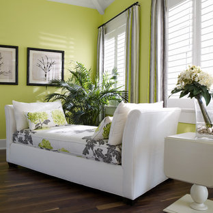 This is an example of a large tropical master bedroom in Tampa with green walls, dark hardwood floors, no fireplace and brown floor.