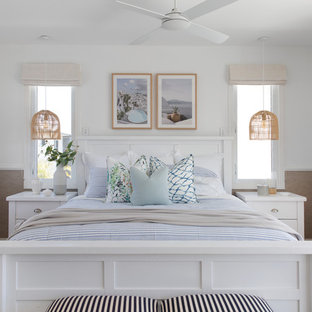 Design ideas for a large beach style master bedroom in Gold Coast - Tweed with white walls, medium hardwood floors and brown floor.