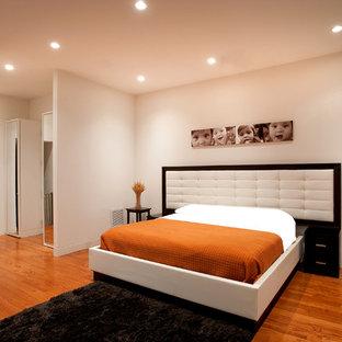 Diseño de dormitorio principal, minimalista, grande, con paredes beige, suelo de madera clara y suelo naranja