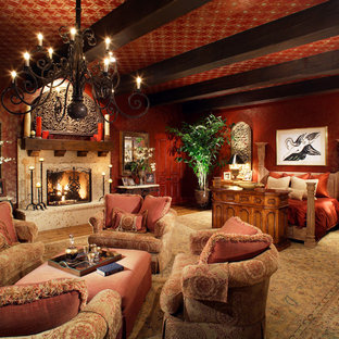 Стильный дизайн: огромная хозяйская спальня в классическом стиле с красными стенами, светлым паркетным полом, стандартным камином, фасадом камина из камня и коричневым полом - последний тренд
