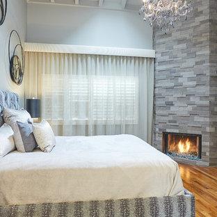 Immagine di una piccola camera matrimoniale minimal con pareti grigie, pavimento in legno massello medio, camino ad angolo, cornice del camino in pietra e pavimento multicolore