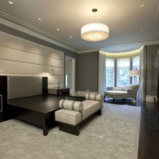Стильный дизайн: большая хозяйская спальня в стиле современная классика с серыми стенами, темным паркетным полом, стандартным камином и фасадом камина из дерева - последний тренд