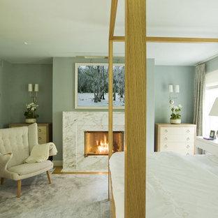 Ispirazione per una camera matrimoniale design con pareti blu e camino classico