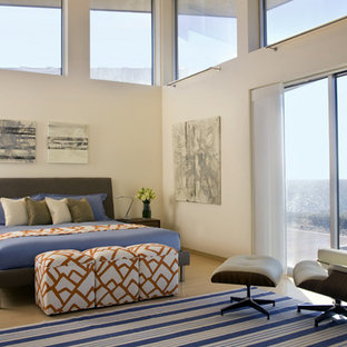 Photo of a contemporary bedroom in Boston with beige walls and medium hardwood floors.