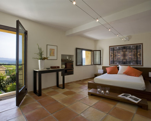 Mediterranean master terra cotta floor and orange floor bedroom idea in  Marseille with beige walls. Bedroom Tile   Houzz