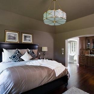 Modelo de dormitorio principal, tradicional, grande, con paredes marrones y suelo de madera oscura