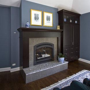 シカゴの広いトラディショナルスタイルのおしゃれな主寝室 (青い壁、濃色無垢フローリング、標準型暖炉、タイルの暖炉まわり、茶色い床、三角天井)