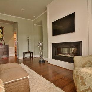 ローリーの巨大なコンテンポラリースタイルのおしゃれな主寝室 (緑の壁、無垢フローリング、横長型暖炉、木材の暖炉まわり)