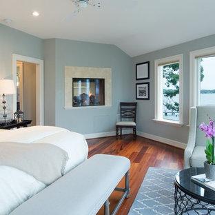 Foto de dormitorio principal, actual, de tamaño medio, con paredes azules, suelo de madera en tonos medios, chimenea de doble cara y marco de chimenea de piedra